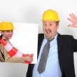 Site's foreman open-mouthed holding picture of woman with construction cone — Stock Photo #9727472
