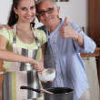 Стоковое фото: Young woman cooking with her grandmother