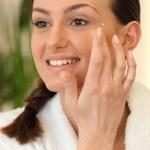 Woman using eye cream — Stock Photo