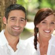 Couple in front of a tree trunk - Stock Photo