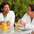 Two men eating breakfast in the garden — Stock Photo
