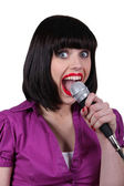 Brunette singing into microphone — Stock Photo