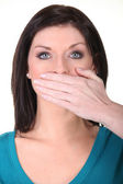Woman with her hand over her mouth — Stock Photo