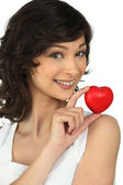 Woman holding a little heart in her hand — Stock Photo