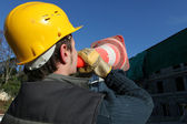 Construction worker shouting through cone — Stock Photo