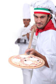 Pizza maker displaying his pizza — Stock Photo