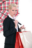 Woman holding shopping backs and umbrella — Stock Photo