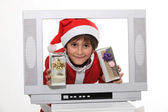 Little boy in Christmas dress behind TV screen — Stock Photo