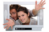 Couple popping out the TV. — Stock Photo