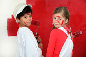 Children painting a wall red — Stock Photo