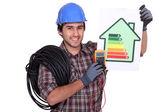 Electricista sosteniendo una etiqueta de consumo de energía — Foto de Stock