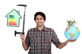 Man holding a globe and an energy efficiency rating chart — Stock Photo