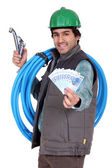 Plumber holding wedge of cash — Stok fotoğraf