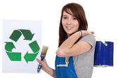 Craftswoman painter holding a recycling label — Stock Photo