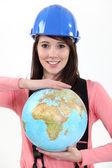 Kvinnliga byggarbetare med en jordglob — Stockfoto