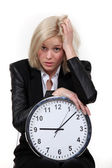 Stressed blond woman with clock — Stock Photo