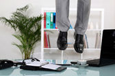 Businessman hanging from ceiling — Stock Photo