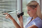 Nyfikna kvinnan tittar fram genom några persienner — Stockfoto