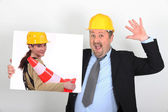 Site's foreman open-mouthed holding picture of woman with construction cone — Stock Photo