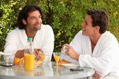 Two men eating breakfast in the garden — Stock Photo