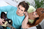 Girl listening to man playing guitar — Stock Photo