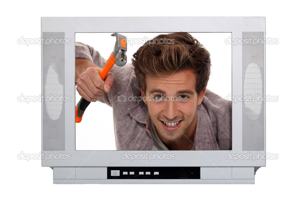 Concept image of a man hammering inside a television  Stock Photo #9724315