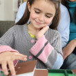 Little girl playing with model house — Stock Photo #9741253