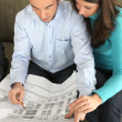 Foto Stock: Couple examining blueprint
