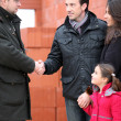 Architect shaking hands with a young family on site — Stock Photo