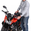 Young man standing next to a motorcycle — Stock Photo