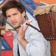 Stock Photo: Young man carrying a djembe