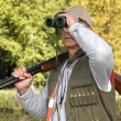 Hunter with rifle looking through binoculars - Stock Photo