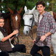 Young boy and girl riding horses — Stock Photo