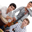 Young men jamming with instruments - Stok fotoğraf