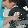 Teenage boy repairing motorcycle — Stock Photo