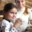 Little girl drinking from large mug at breakfast — Stockfoto