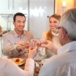 Four adults making a toast at dinner — Stock Photo #9743756