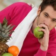 Pensive young man eating fruit — Stock Photo