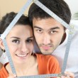Stock Photo: Couple with meter forming a house