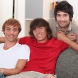 Stock Photo: Three young men on sofa