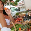 Woman buying fruit in market - Stock Photo