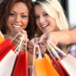 Women holding out their shopping bags — Stock Photo