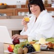 Woman having breakfast in the kitchen — Stock Photo