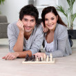 Couple playing chess lying - Stock Photo