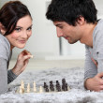 pareja jugando al ajedrez tumbados en la alfombra — Foto de Stock   #9746670