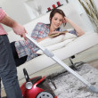 Husband vacuuming whilst wife lays on sofa — Stock Photo #9746996