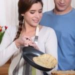 Couple cooking pancakes — Stock Photo