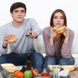Portrait of young couple eating burgers while watching TV - Stock Photo