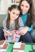 Mother and daughter sat by scale model of housing — Stock Photo
