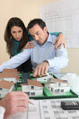 Architects gathered around model replica of housing estate — Stock Photo